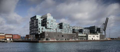 The school building's unique facade is covered in 12,000 solar panels, each individually angled to create a sequin-like effect,