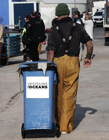 fisherman holding upcycling the oceans trash container